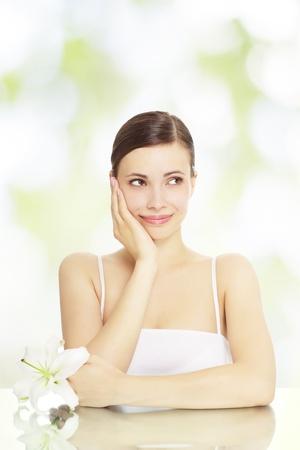 Bella ragazza con fiori di giglio su uno sfondo verde