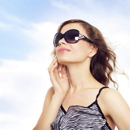Happy young lady smiling with sunglasses. Sky background Stock Photo