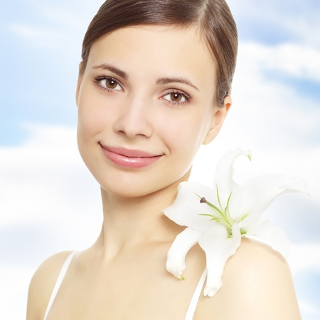 Beautiful girl with lily flower. Sky background photo