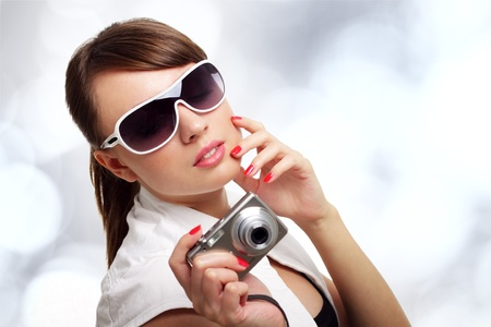 Young stylish woman with a camera on a light background Stock Photo - 9824110