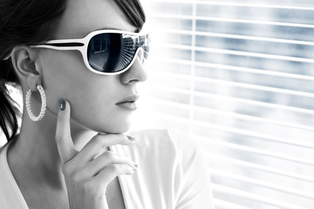 Young woman wearing sunglasses on a light background Stock Photo - 9824081