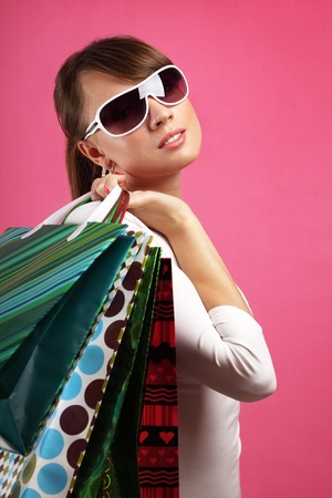 Stylish Girl with shopping bags on red background Stock Photo - 9824226