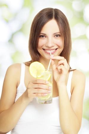 fruit drinks: girl holding a lemonade on a light background
