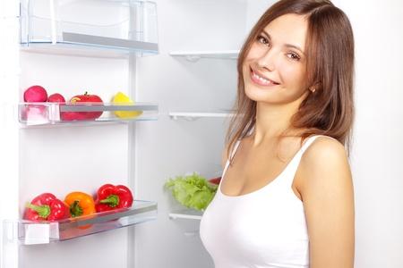 nevera: Recogiendo alimentos de la nevera. Verduras en la nevera
