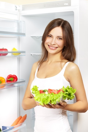 refrigerator: Young woman with healthy salad. background refrigerator