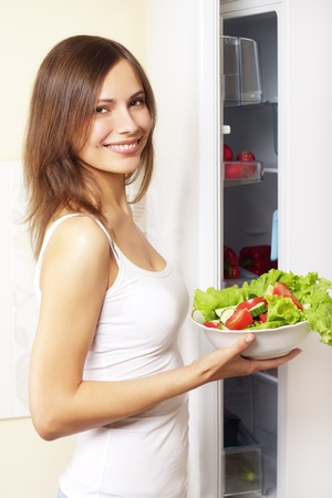 Young woman with healthy salad. background refrigerator photo