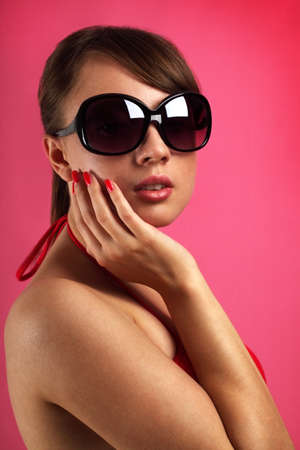 Young woman wearing sunglasses on red background photo