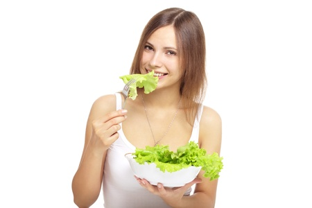 green leafy vegetables: Young woman eating healthy salad isolated on a white background Stock Photo