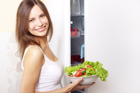 green leafy vegetables: Young woman with healthy salad. background refrigerator