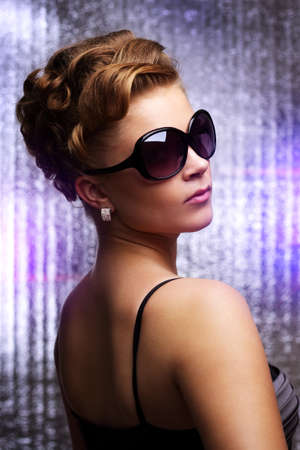 Young woman wearing sunglasses. On colored background photo