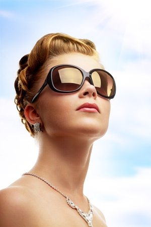 Young woman wearing sunglasses. Sky background photo