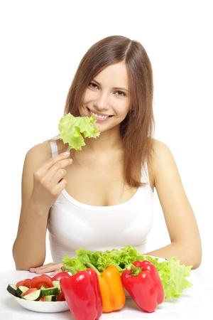 Junge Frau isst gesunden Salat auf einem weißen Hintergrund Standard-Bild - 9955318