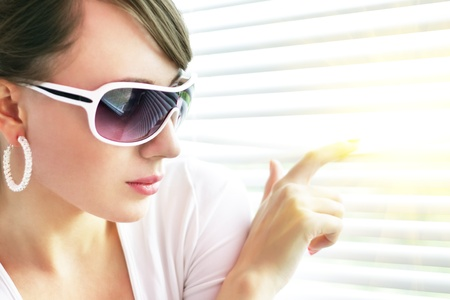 stylish girl looking through the blinds photo