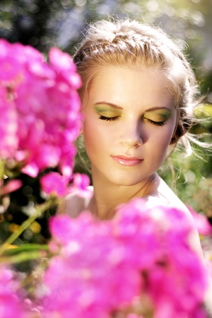 Young woman with summer make-up. pink phlox flowers photo