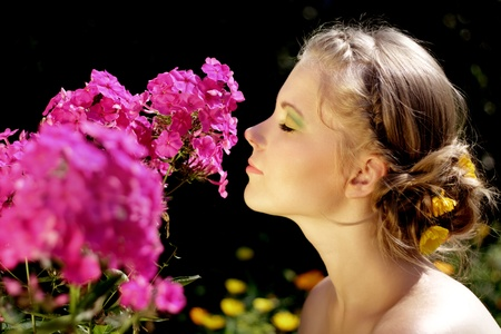 Girl and pink phlox flowers on dark background
