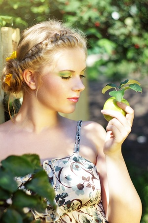 Young woman holding a green apple on a light background photo