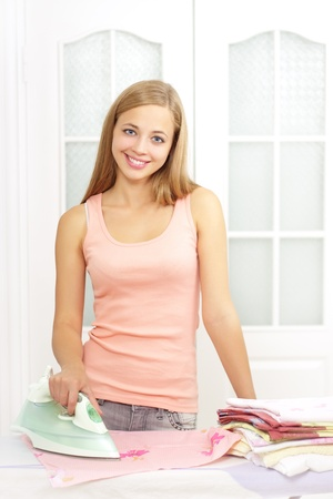 teen girl underwear: beautiful girl with an iron on the light background