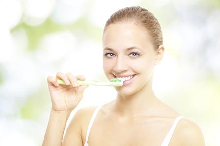 Girl brushing teeth on a light background photo