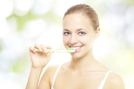 Girl brushing teeth on a light background photo