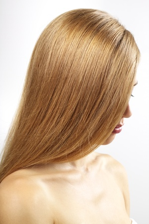 blond brown: Girl with beautiful straight hair on a gray background