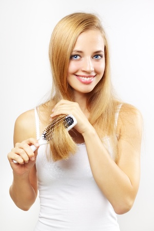 girl combing of her hair on a light background photo