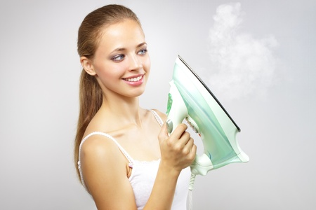 steam jet: Smiling girl with iron on gray background