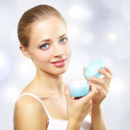 girl holding a box of cosmetic cream on a light background photo