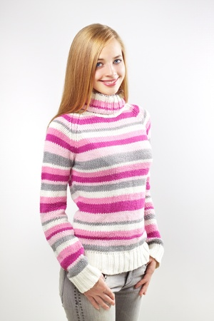 Portrait of pretty girl wearing sweater on a gray background
