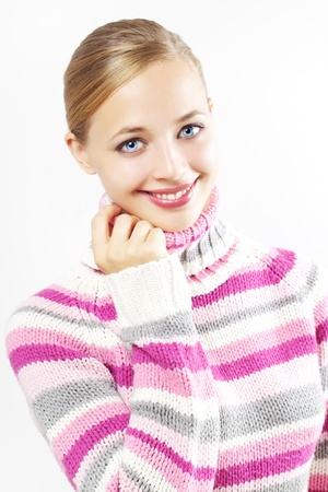 beautiful girl in colored sweater on a light background