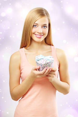 beautiful girl with gift box on light background photo