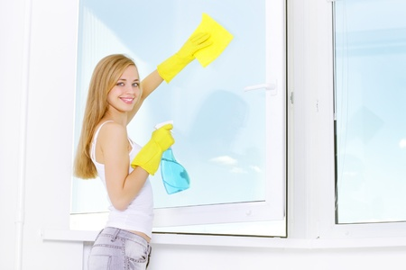 Domestic cleaning: smiling girl washing windows at home Stock Photo