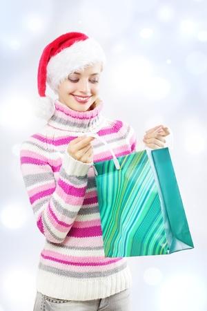 Santa girl holding shopping bag on a light background photo