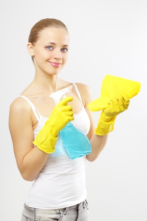 Woman holding glass cleaner and rag. gray background photo