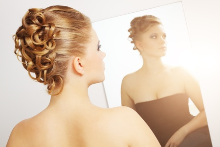 Modern wedding hairstyle. Reflection in the mirror photo