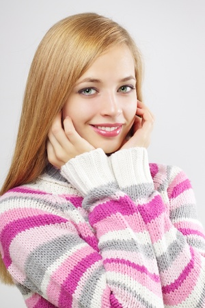 Portrait of pretty girl wearing sweater on a light background photo