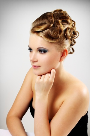 Portrait of a girl with beautiful hairstyle on a gray background photo