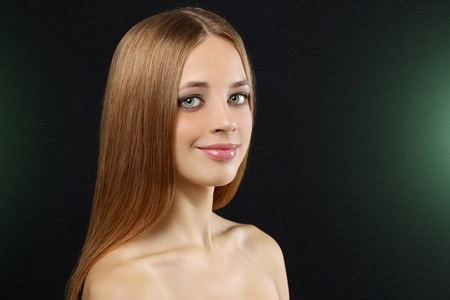 Attractive girl with beautiful, straight hair on a dark background Stock Photo - 10798401