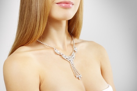 woman with beautiful necklace on a light background