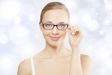myopia: Girl wearing eyeglasses. Light blue background Stock Photo