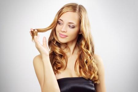 Schöne Mädchen mit langem, welligem Haar vor einem grauen Hintergrund Standard-Bild - 10798394