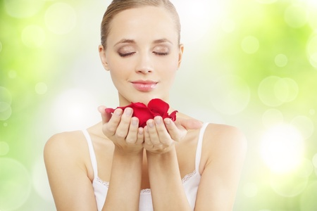 Pretty girl with rose petals on a green background photo