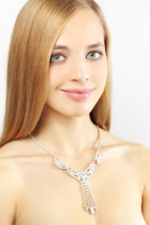Portrait of a beautiful girl with necklace on a gray background photo