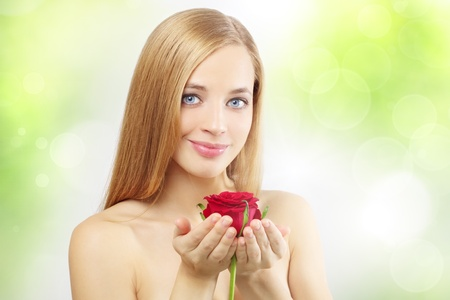 beautiful girl with red rose on a green background photo