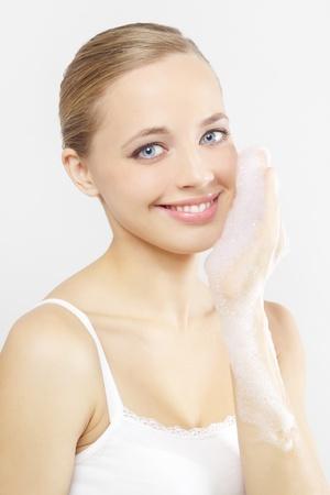 Donna, lavarsi la faccia su uno sfondo grigio Archivio Fotografico - 10798416