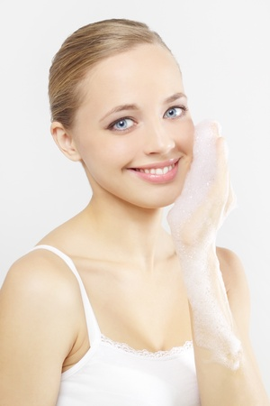 foam hand: Woman washing her face on a gray background Stock Photo