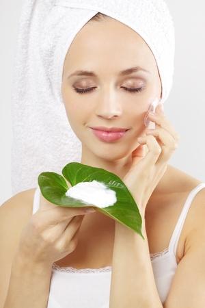 Junge Frau, die Anwendung kosmetische Creme auf einem grauen Hintergrund Standard-Bild - 10798419
