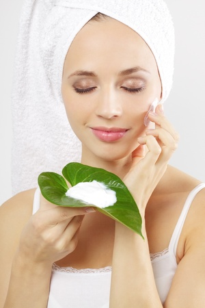 Young woman applying cosmetic cream on a gray background