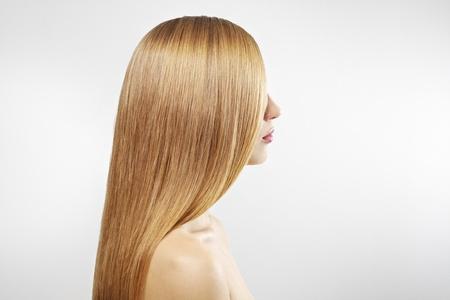cabello lacio: Ni?a con hermoso cabello lacio sobre un fondo gris Foto de archivo