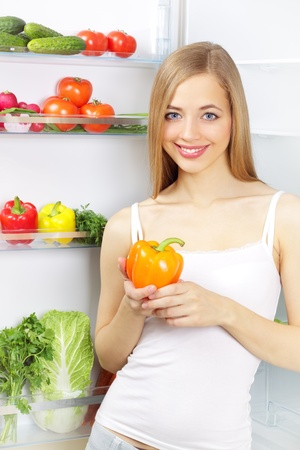 Picking food from fridge. Vegetables in the refrigerator photo