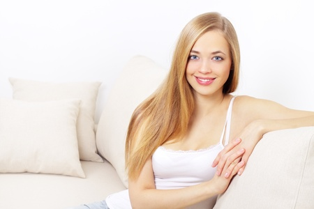 smiling girl sitting on sofa on a light background Stock Photo - 12235291